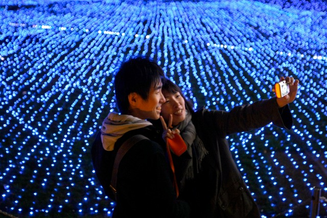 A couple snaps a souvenir shots in front of the illumination ahead of the Christmas at Tokyo, Japan, Friday, Nov. 20, 2009. (AP Photo/Shizuo Kambayashi)